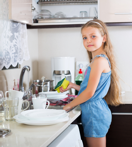 Independent little girl doing dishes in kitchen at home